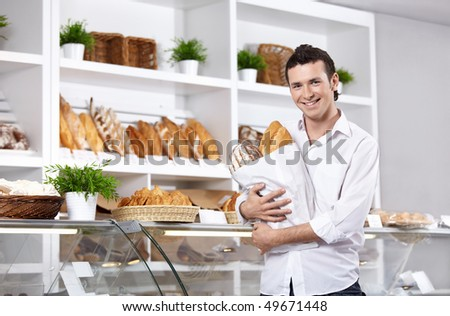 The young man with bread in shop - stock photo
