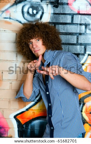 The young man with curly hair against a brick wall of graffiti - stock photo
