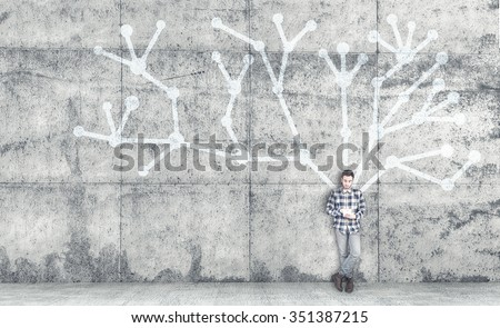 The young man with the tablet, next to a blackboard with chalk Network - stock photo