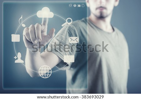 The young man works with huge touch screen, icons placed in circle - stock photo