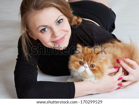 The young nice girl holds a red Persian cat on hands