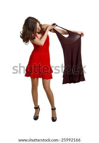 The young nice woman in a red dress with the same dress of brown color in hands. Isolation on a white background - stock photo