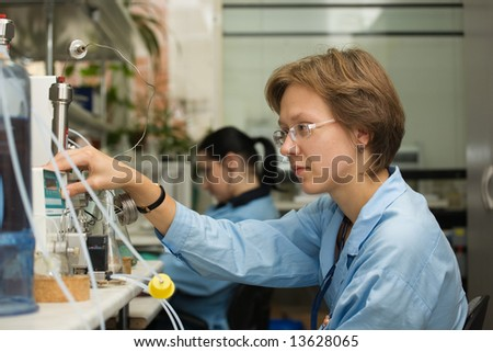 The young nice woman-scientist work with scientific instrument on a background scientific instruments - stock photo