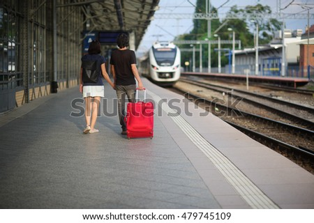 The young pair standing on platform having joined hands. The young man rolls a red suitcase. Both look at a train which comes close.