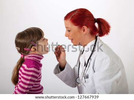 The young pediatrician looks a little girl in the mouth - stock photo