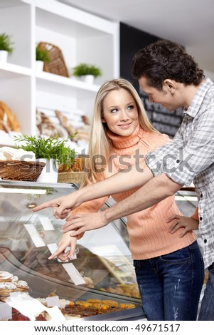The young people buy bread in shop - stock photo