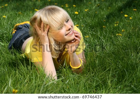 The young pretty girl lies on a glade of dandelions and rejoices to the sun and spring heat - stock photo