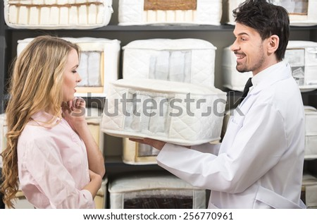 The young salesman tells the customer about quality mattresses in the store. - stock photo