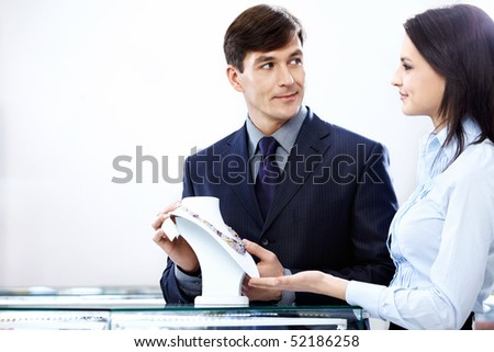 The young saleswoman shows a jeweller necklace - stock photo