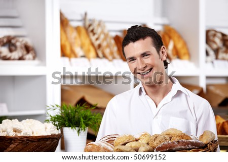 The young seller with a basket of rolls close up - stock photo