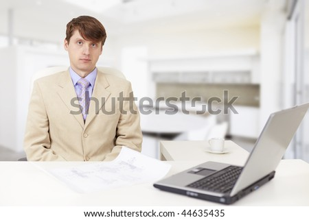 The young serious businessman on a workplace with the laptop