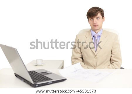 The young serious person on a workplace with the laptop - stock photo