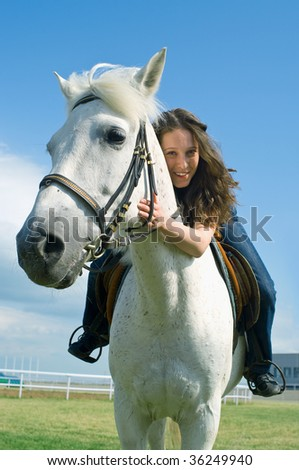 The young smiling girl embraces a white horse - stock photo