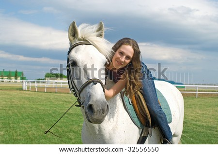 The young smiling girl embraces a white horse. Summer landscape - stock photo