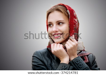 The young smiling woman in a red scarf on walk isolated on grey background.