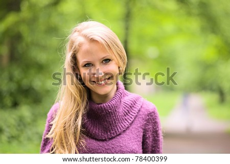 The young smiling woman in park. - stock photo