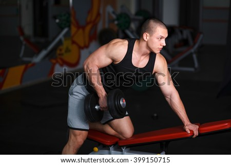 The young strong man doing fitness in the gym. Perform exercises with dumbbells.