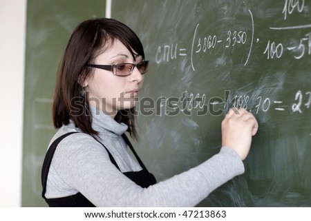 The young student in glasses writes on a board - stock photo