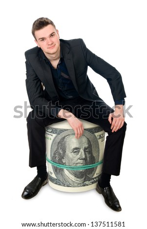 The young successful businessman sitting on a roll of money. Isolated on white background - stock photo