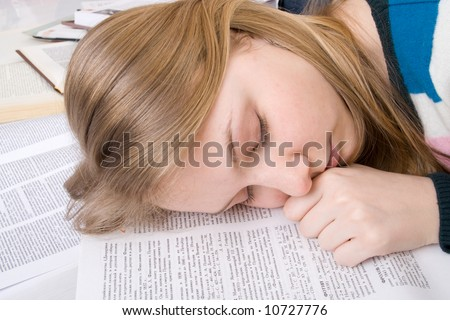 The young tired student sleeps on books