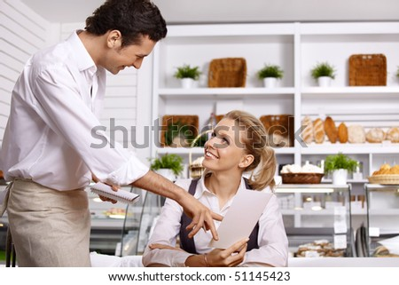 The young waiter advises to the girl a dish choice - stock photo