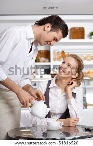 The young waiter pours tea to the client in cafe - stock photo