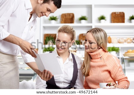 The young waiter shows the menu to two girls - stock photo