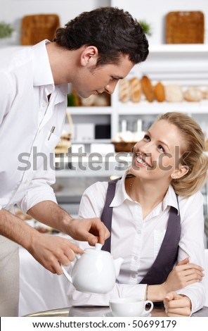 The young waiter with the client in cafe - stock photo