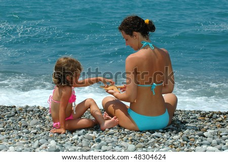 The young woman and child with cockleshell sit on a beach - stock photo