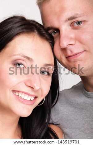 The young woman and the man in passionate embraces couple gray wall - stock photo