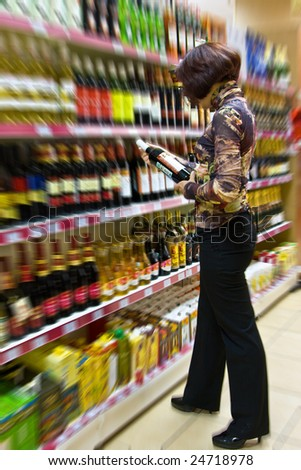The young woman chooses wine in a supermarket - stock photo
