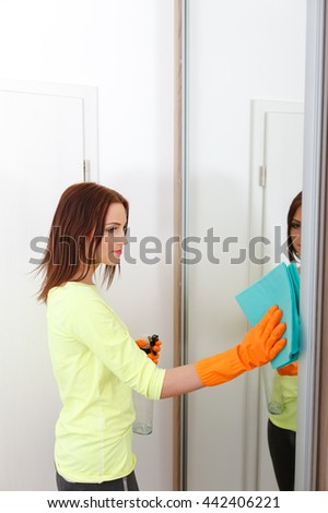 The young woman cleans a bathroom. Girl cleans shower and mirror using detergents. When it uses protective gloves. - stock photo