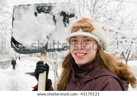 The young woman cleans snow from sidewalk. - stock photo