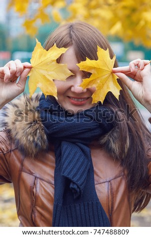 The young woman covered her face with two yellow maple leaves.