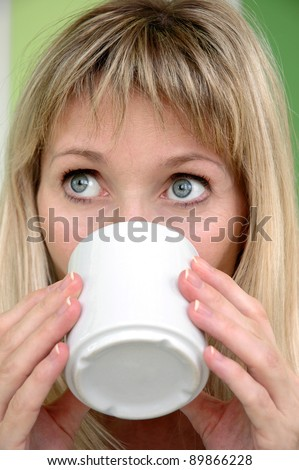 The young woman drinks from a mug