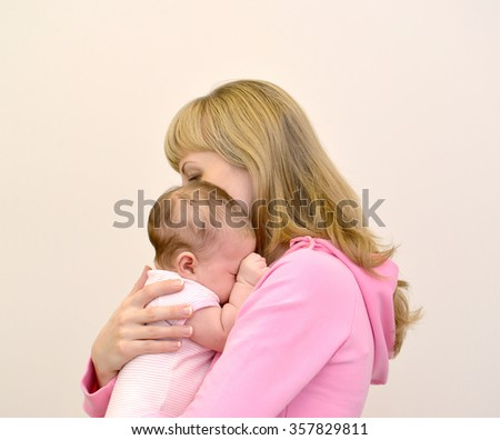 The young woman embraces the crying baby - stock photo
