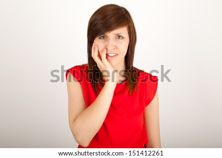 The young woman has got toothache and is holding her cheek