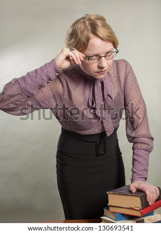 The young woman has put a hand on a pile of books - stock photo