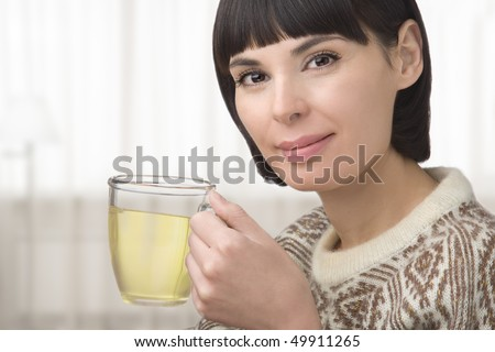 The young woman holds in hand a cup with green tea - stock photo