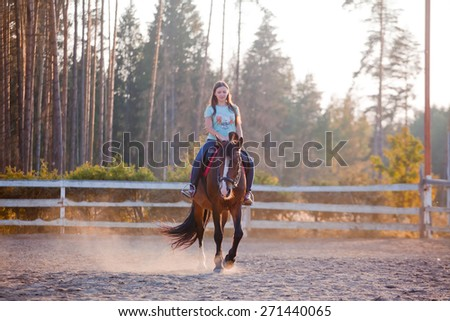 The young woman horseback riding at summer evening - stock photo