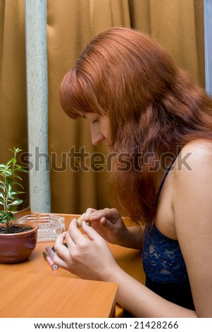 The young woman in a dark blue peignoir does manicure