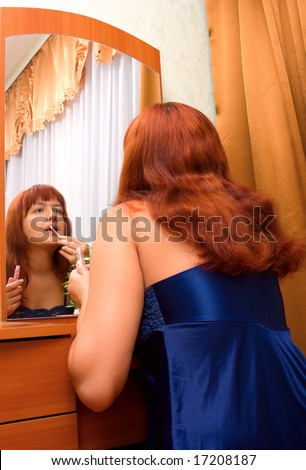 The young woman in a dark blue peignoir tints lips lipstick before a mirror in a room