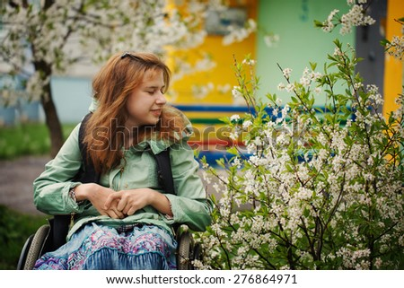 The young woman in a wheelchair inhales aroma of the blossoming cherry in the warm spring afternoon - stock photo