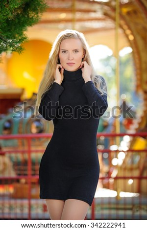 The young woman in black short dress against the carousel - stock photo