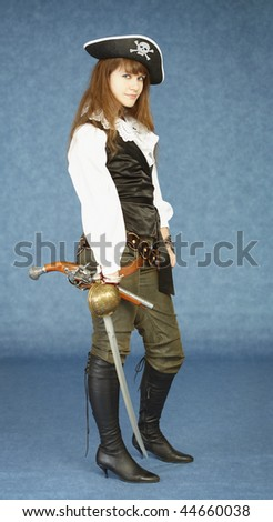 The young woman in clothes of the pirate on a dark blue background - stock photo