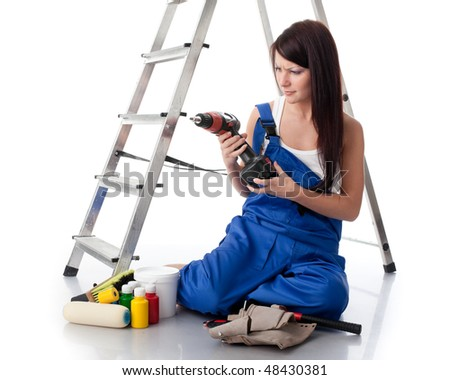 The young woman in overalls sits with various building tools near a step-ladder on a white background. - stock photo