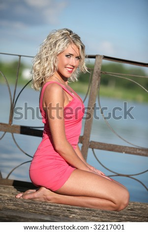 The young woman in pink clothes on river quay. - stock photo
