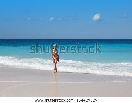 The young woman in the New Year's cap walks on a beach
