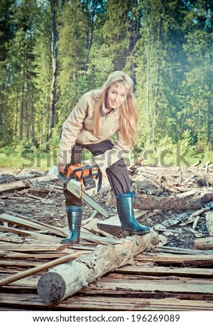 The young woman in wood saws a tree a chain saw,with a retro effect  - stock photo