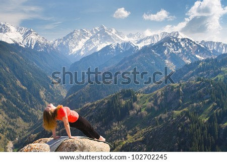 The young woman is doing a yoga asana on the summit. On the background is a range of high tops of mountains. - stock photo